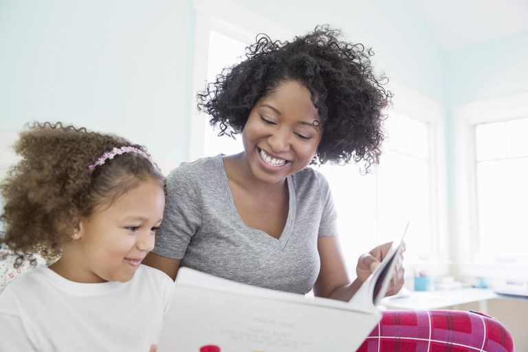 Happy mother and daughter reading book in bedroom