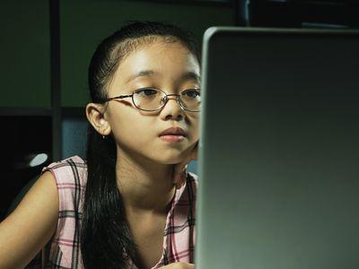 Schoolgirl (10-12) using laptop computer, close-up
