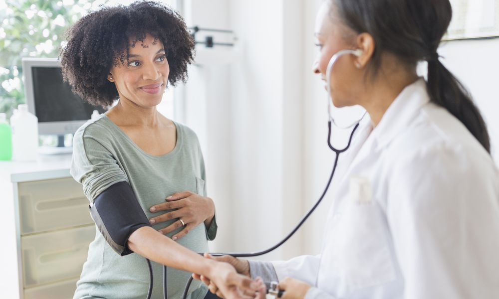 African American doctor taking pregnant woman's blood pressure