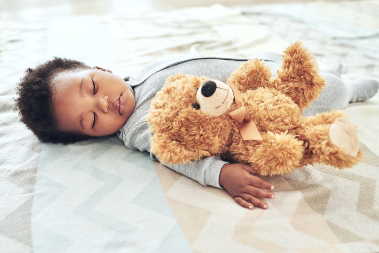 Baby wearing onesie sleeping on bed with teddy bear