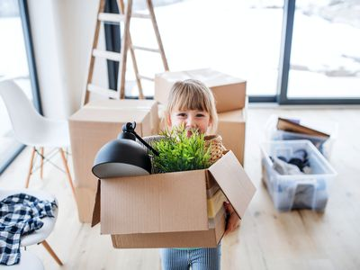 Little girl carrying a moving box holding a lamp and plant.