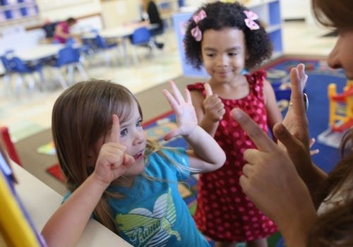 Two preschool-age girls counting on hands with teacher