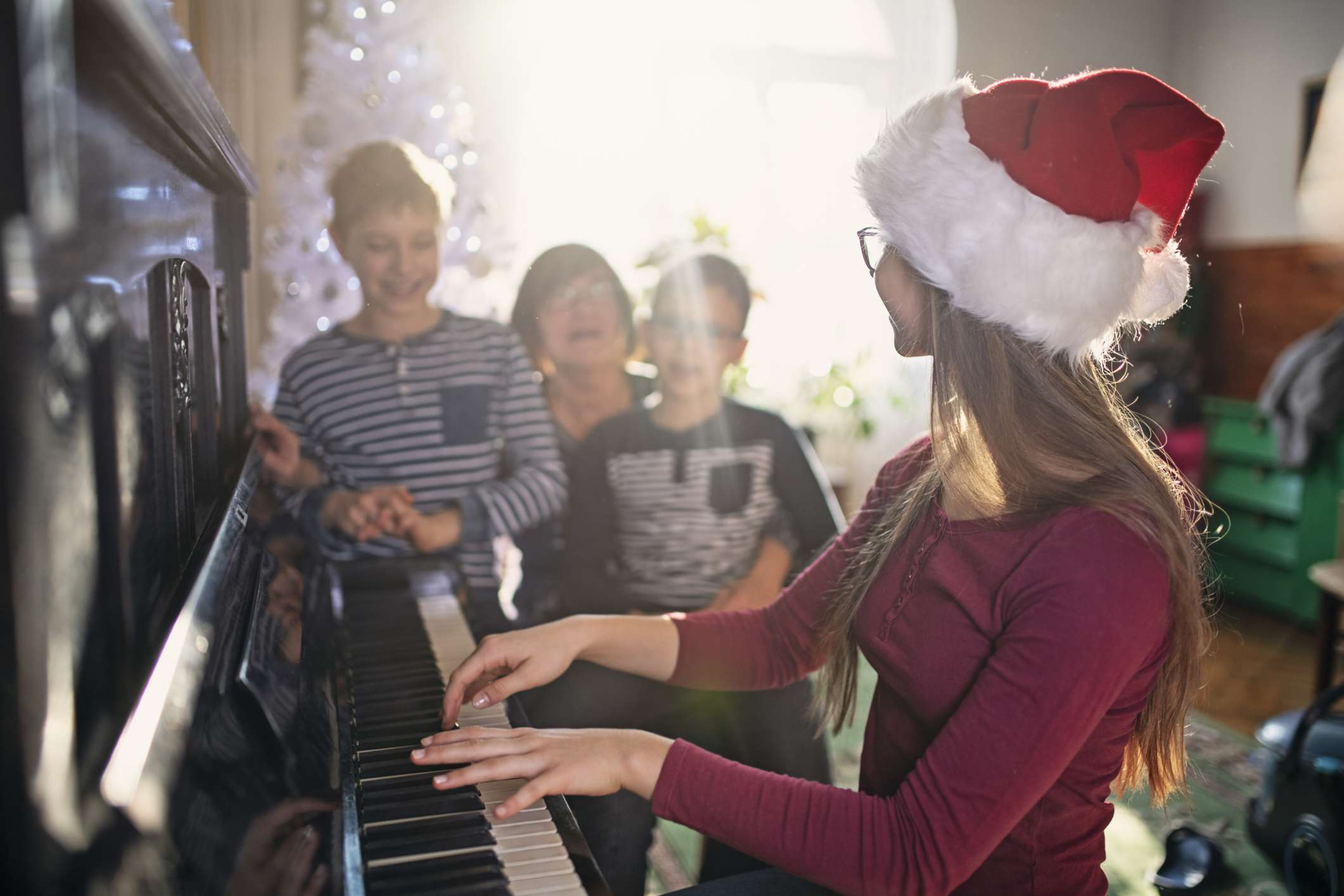 Girl playing piano and family singing Christmas songs