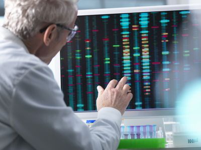 Scientist comparing DNA results on a computer screen in the laboratory