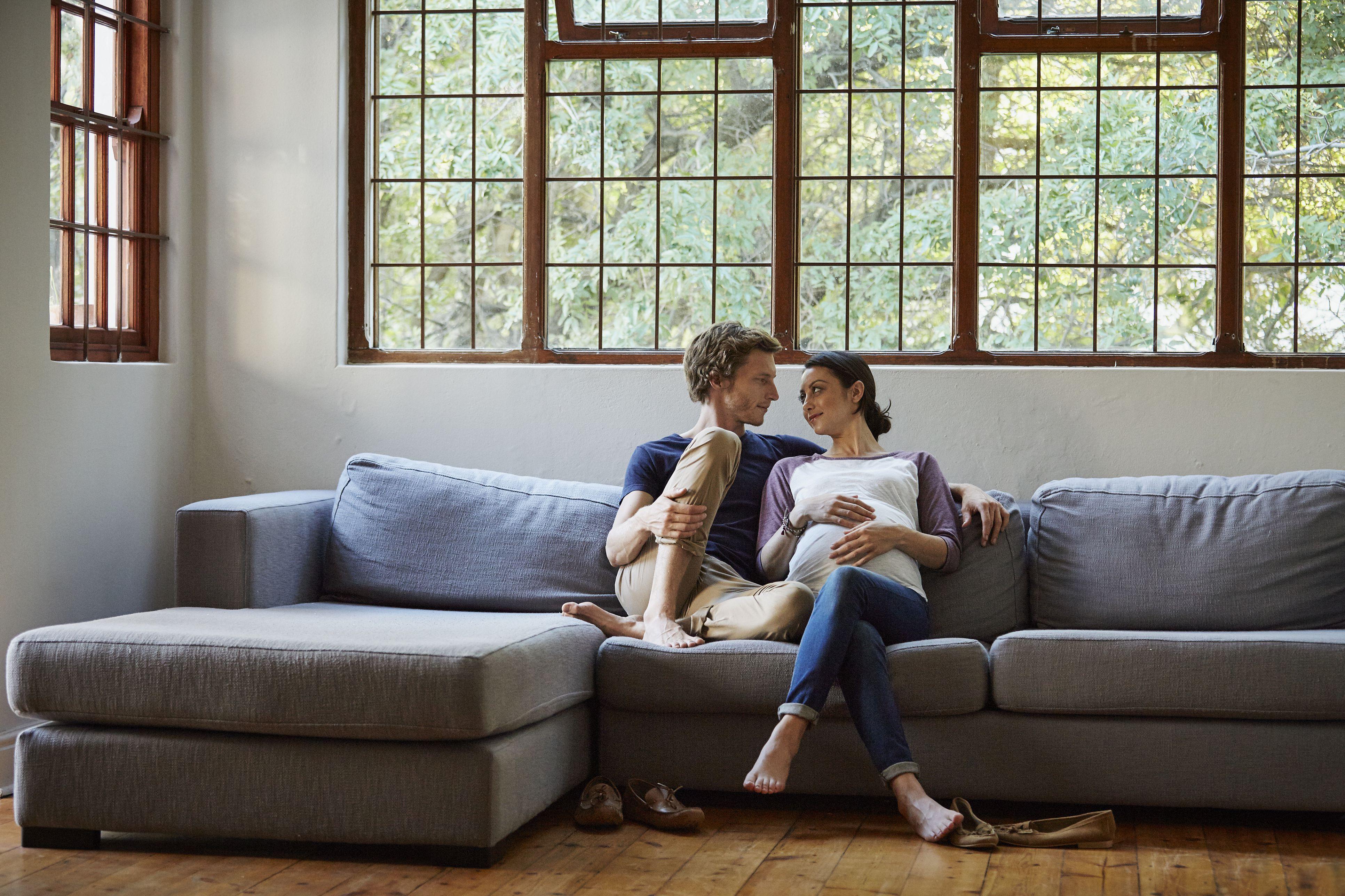 expectant couple sitting on sofa