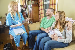 Family with newborn talking with lactation specialist