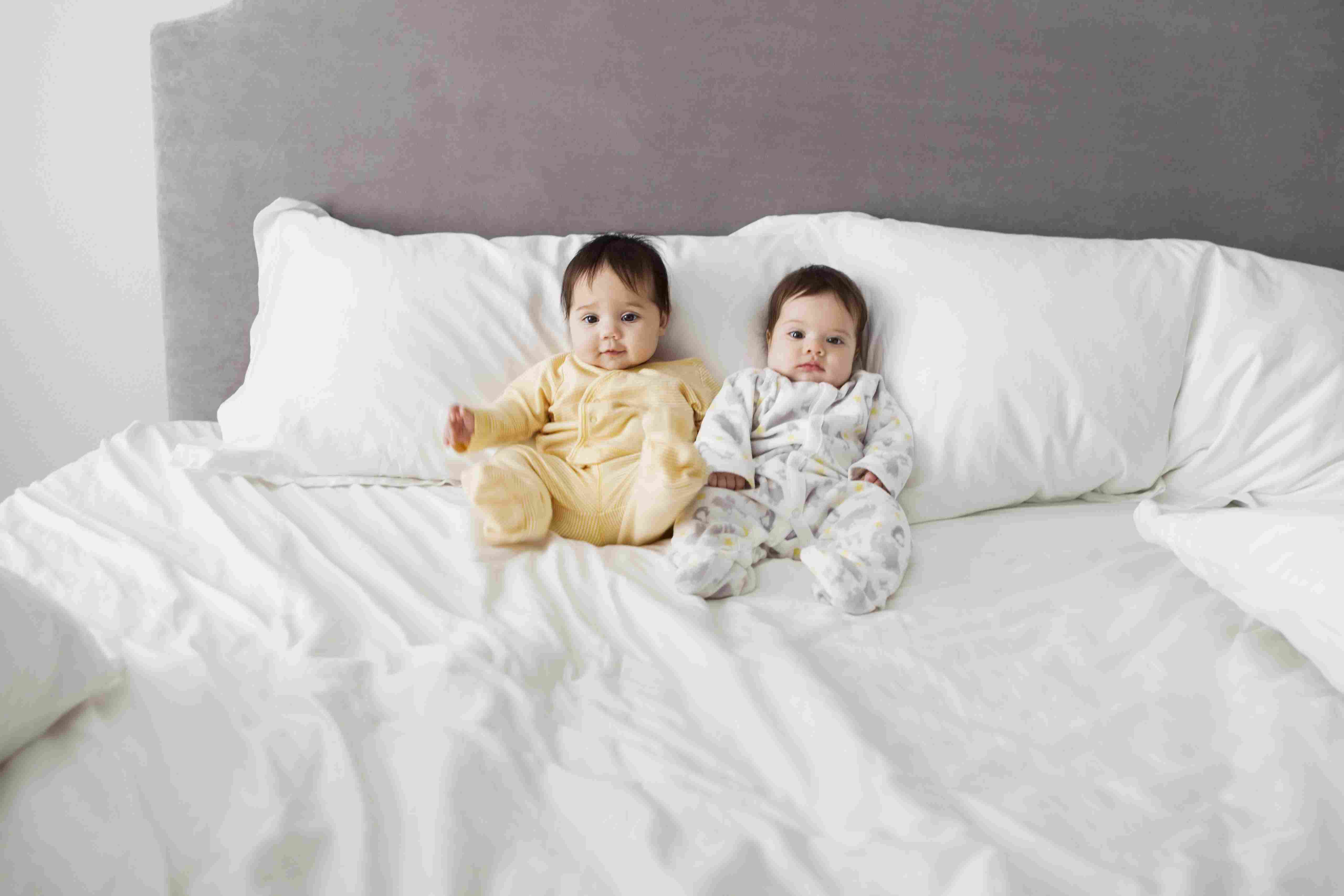twin baby girls sitting on bed