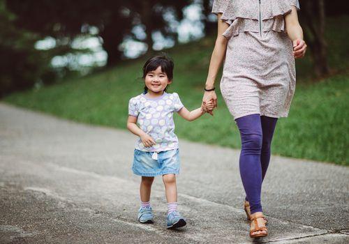 Little girl strolling in park with mom joyfully