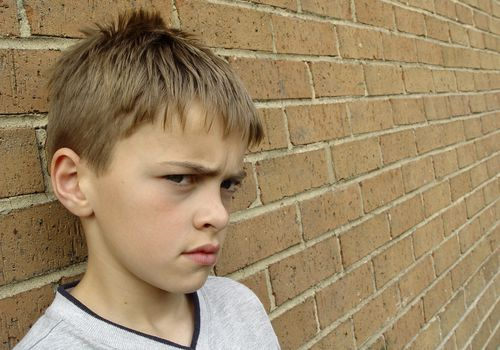 defiant little boy standing against a brick wall