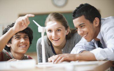 Teenage students looking at model windmill in classroom