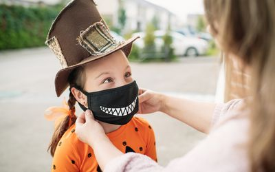 Child wearing face mask with Halloween costume