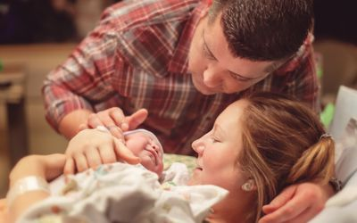 couple looking at their newborn baby for the first time
