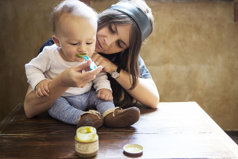 Young Mother Feeding Baby Boy At Table