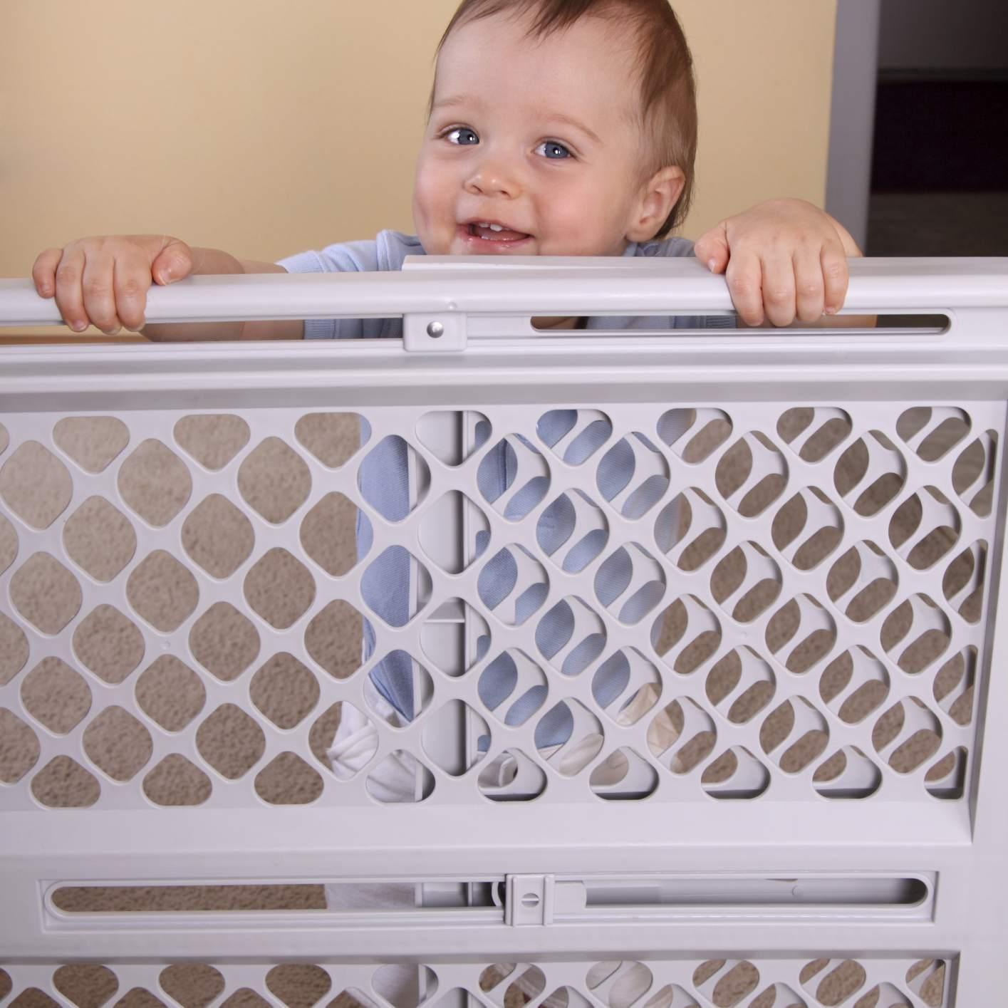 Toddler standing behind baby gate.
