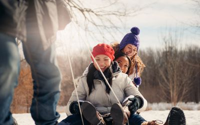 Teenagers being pulled on a sled