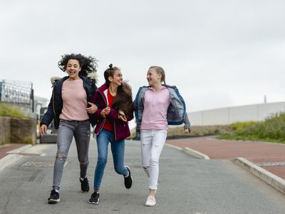Three cheerful teenage girls arm in arm