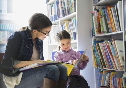 woman and girl reading at library