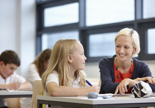 Teacher working with schoolgirl in classroom