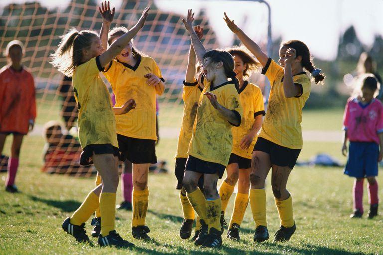 Football, girls (8-12) celebrating goal