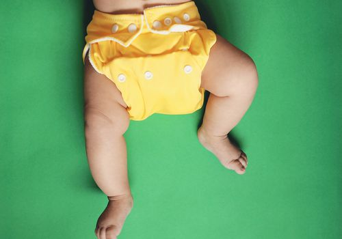 Baby wearing yellow cloth nappy or diaper