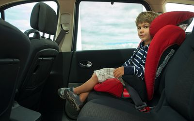 Little boy sitting in high back booster car seat fasten with seat belt.
