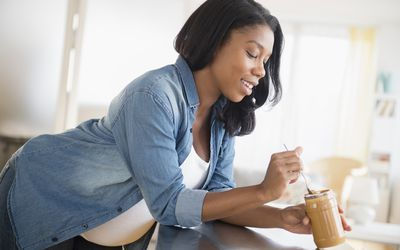 Pregnant woman eating peanut butter in kitchen