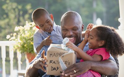 father with kids opening gift
