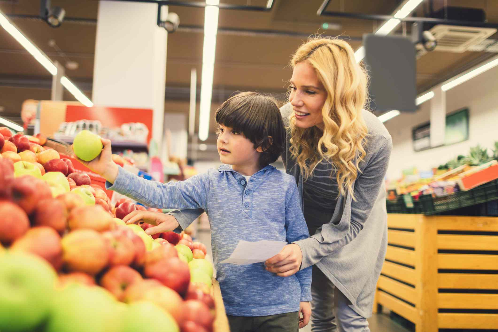 Mother and son picking out apples at the grocery store