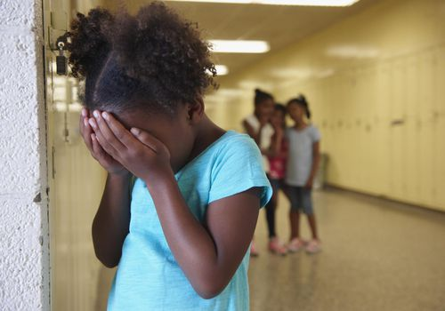 Bullied young girl in school hallway