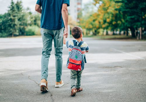 Rear view of father who leads a little boy hand in hand to kindergarten. Father and son with backpack walking in schoolyard.