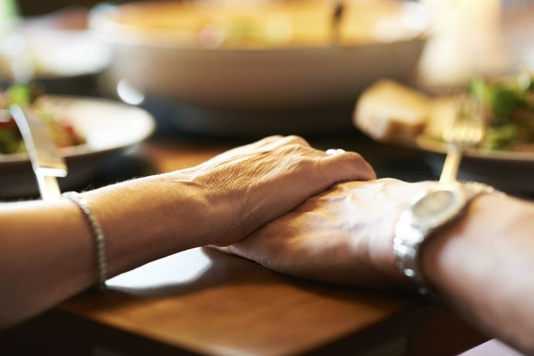 Couple holding hands at dinner party, supporting each other during infertility