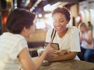 Young women friends using cell phone and drinking coffee in cafe