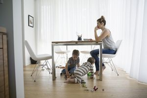 Brothers playing with toys under mother working at laptop