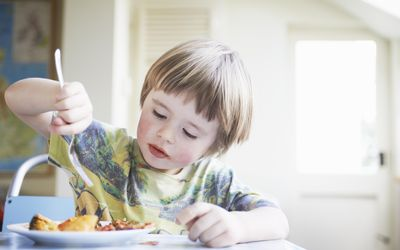 Young boy eating dinner in kitchen