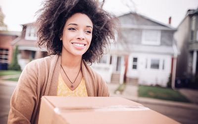 college-aged young woman holding a cardboard box