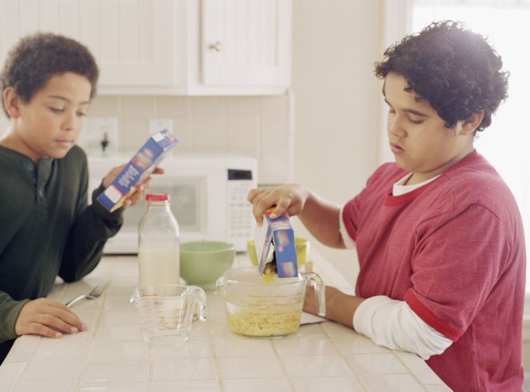 Two boys making instant macaroni and cheese