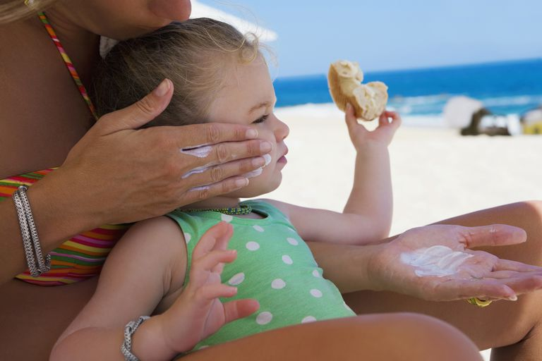 Woman applying suntan lotion to her daughter,Cabo San Lucas,Mexico