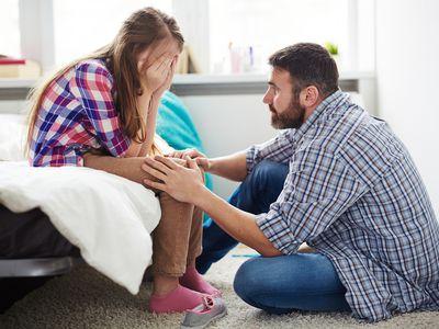 dad comforting teen daughter