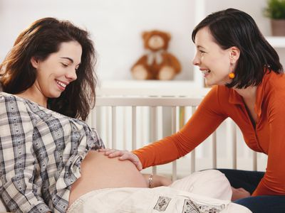 Doula with hand on pregnant woman's belly