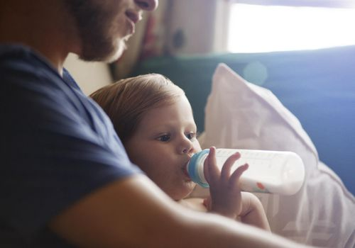 Father Holding Baby Drinking Out Of Bottle