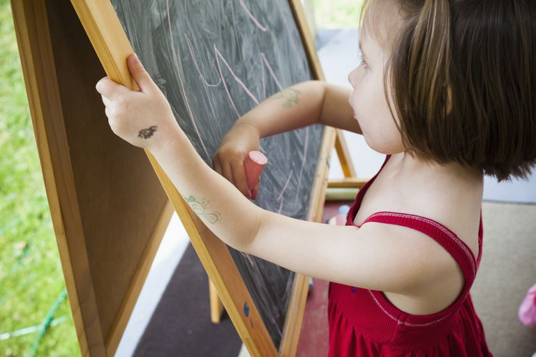 little girl drawing on chalk board easel