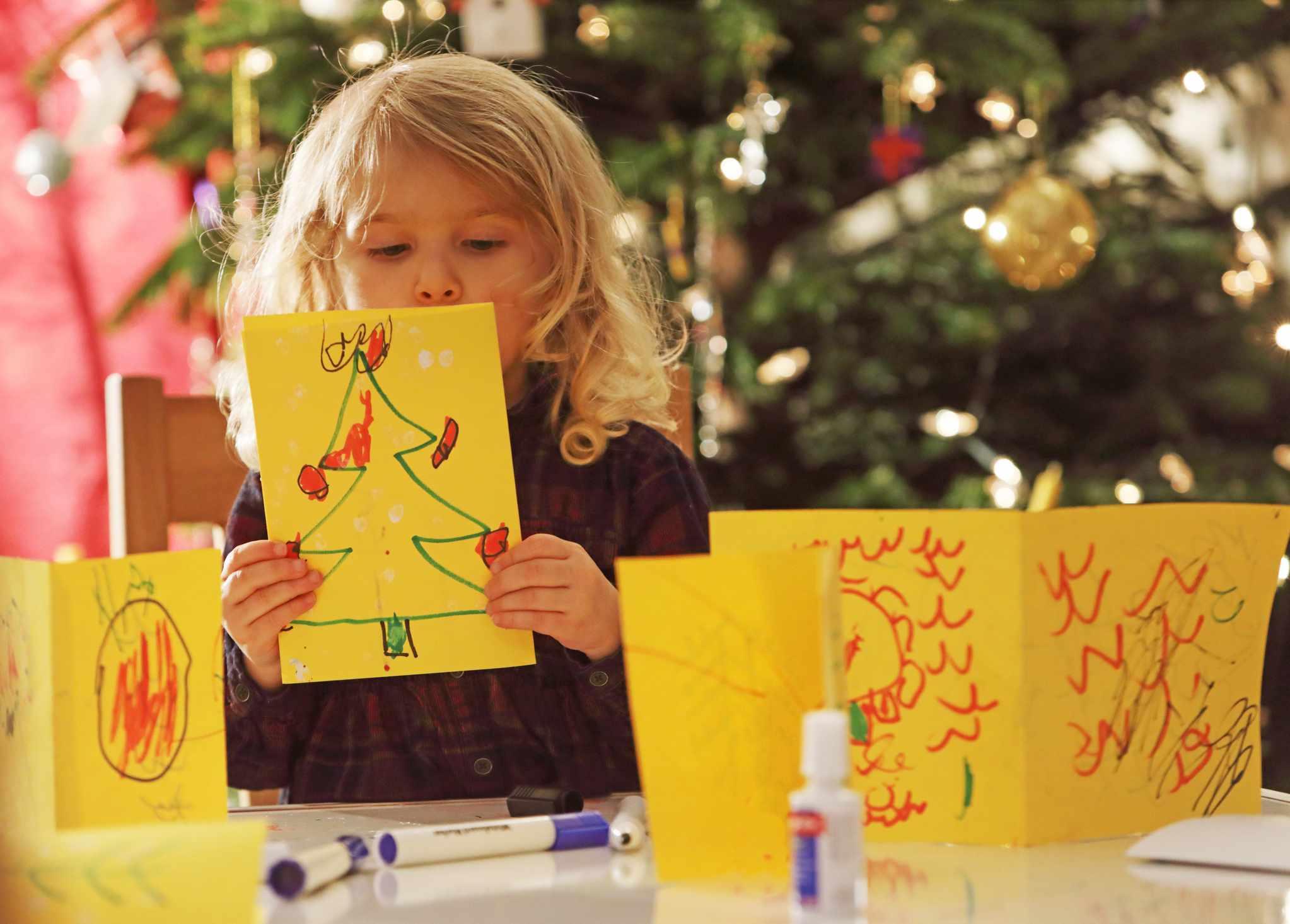 Young girl making homemade Christmas cards