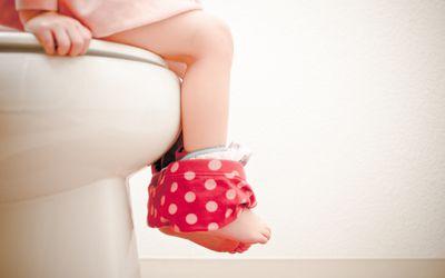 toddler girl sitting on toilet