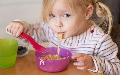 Toddler girl eating noodles from bowl