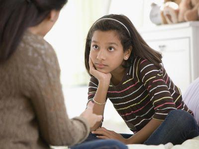 Mother talking to daughter in bedroom.