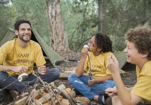 A camp counselor and two kids eating fried marshmallows