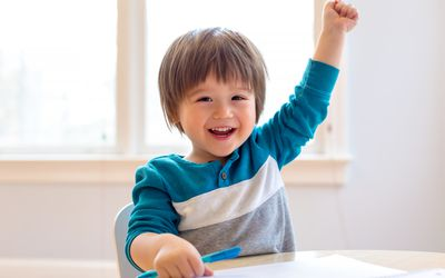 Toddler smiling and raising his hand at a desk while holding pen with his other hand