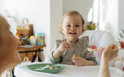 Cheerful baby girl eating meal with mother