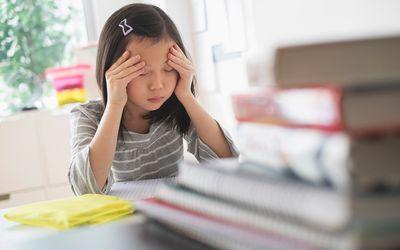 Anxious Chinese student rubbing forehead doing homework