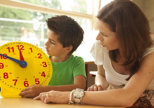 Little boy and teacher looking at a large clock